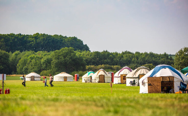 Traditional yurts with different colours are spaced out in Kelmarsh Estate, with trees in the background.
