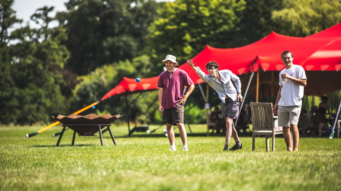 Three men stand in a row playing boules on the green