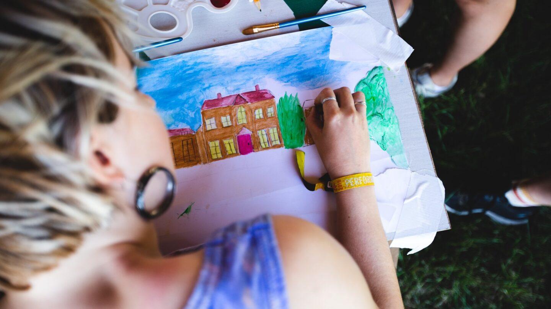 An overshoulder shot of a woman drawing a scene of Kelmarsh Hall