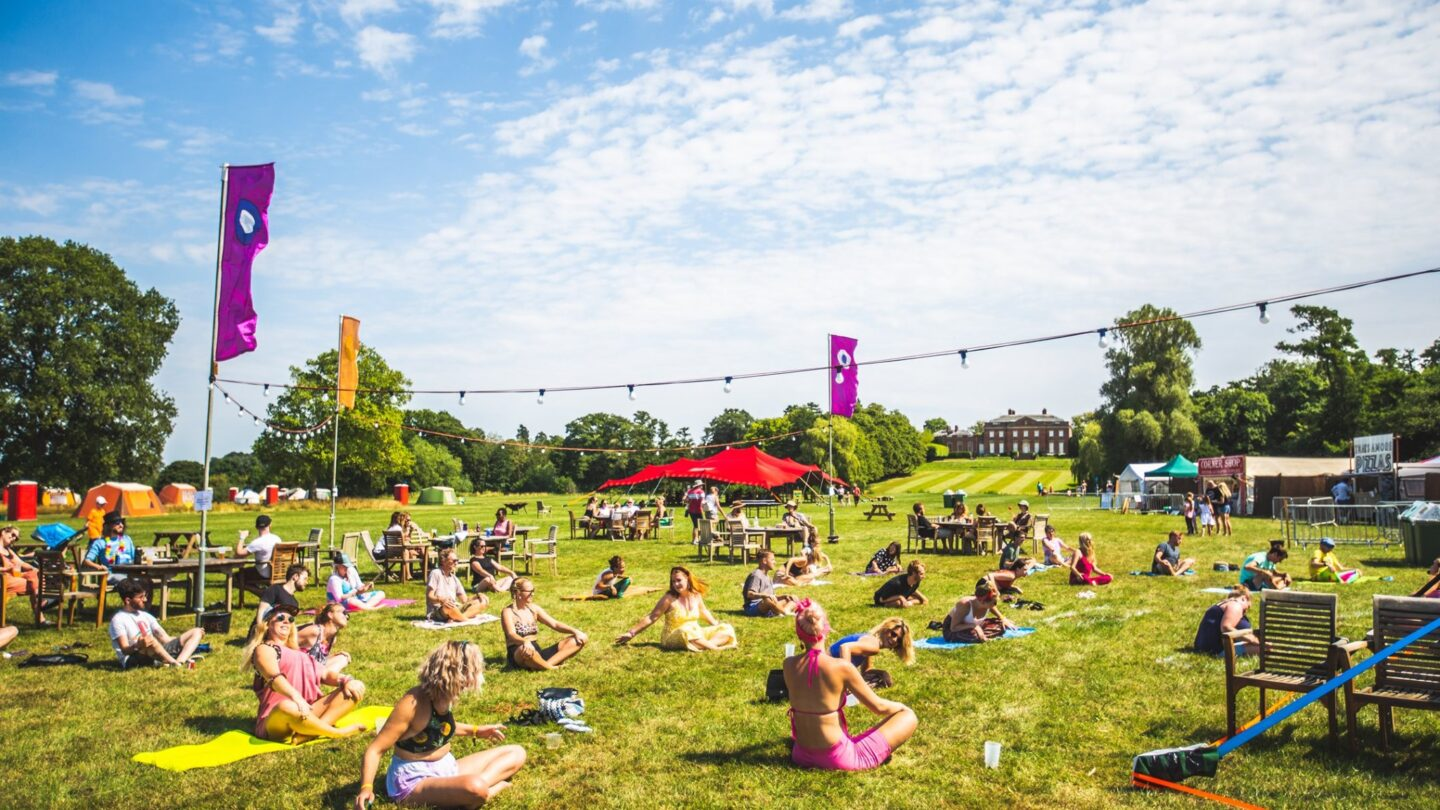 A group of people participate in socially distanced yoga in the meadow overlooking Kelmarsh Hall