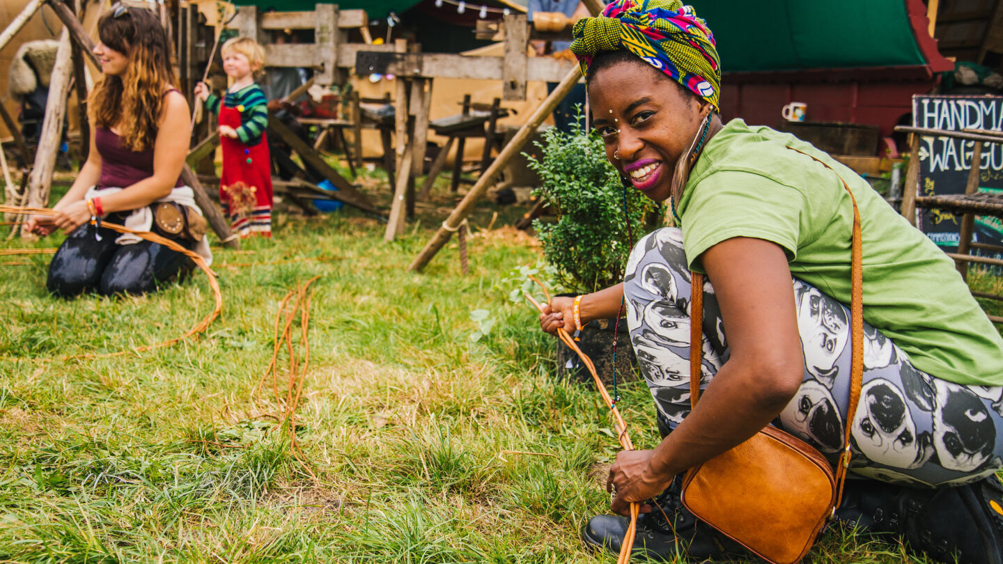 A woman with a headscarf smiles as she crafts with willow