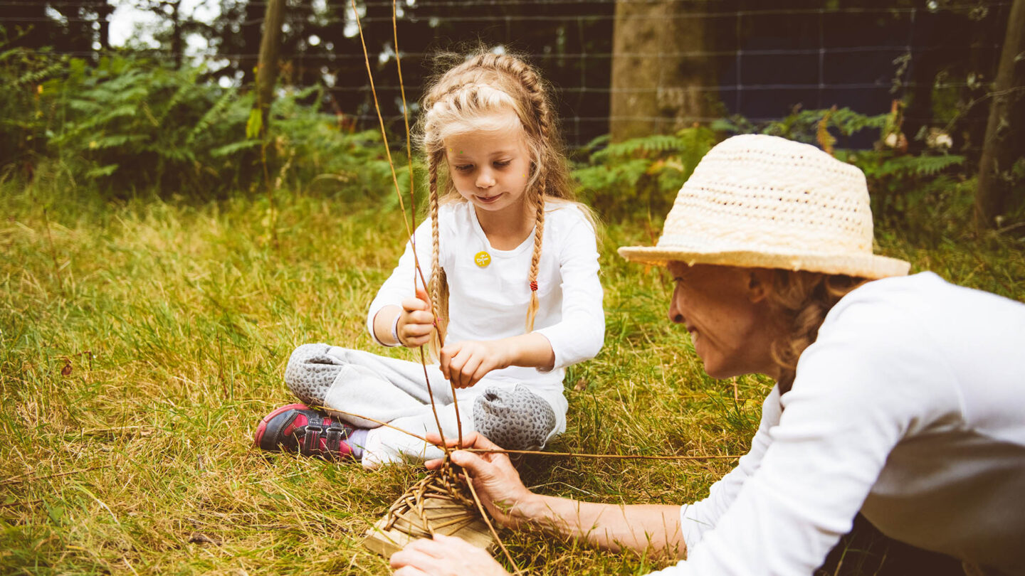 A young girl sits crossed legged twisting willow, while an older women holds the weaved based secure.
