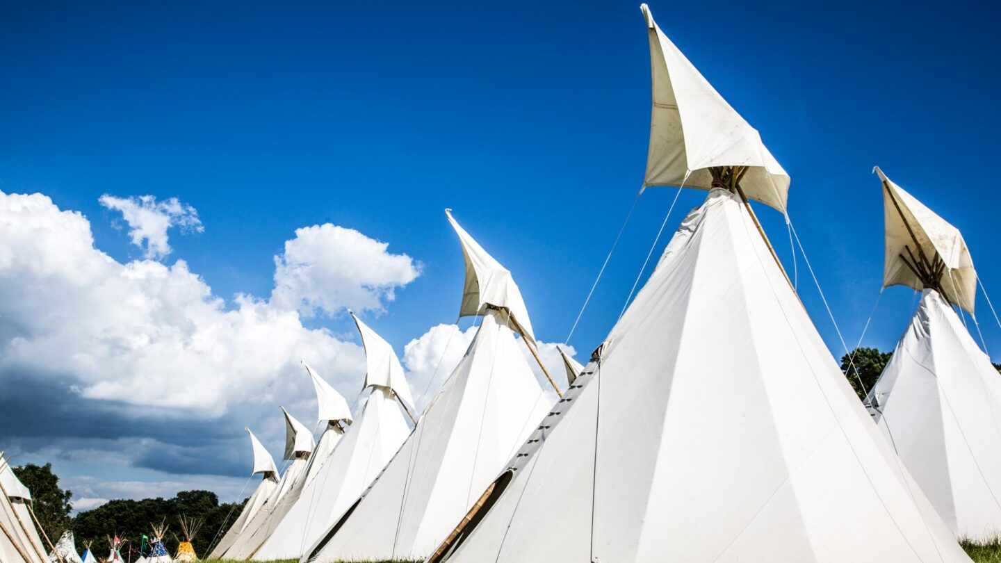 A row of beautiful handcrafted traditional tipis against a bright blue sky.
