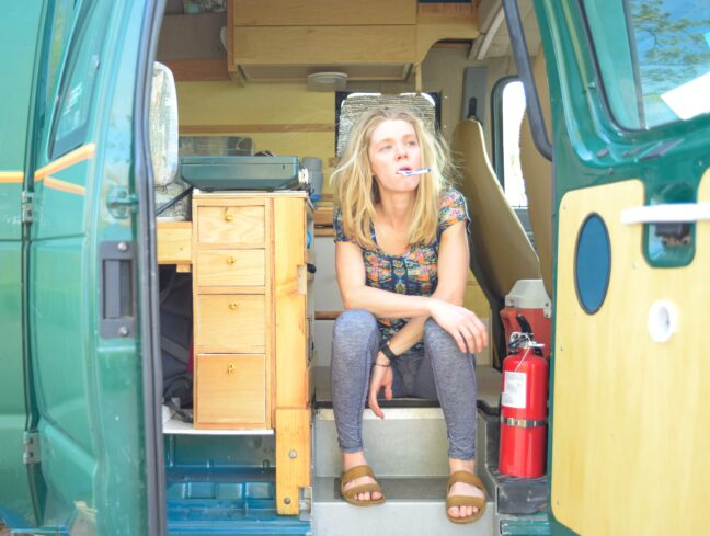A blonde woman sits in a converter van with the side doors open. She has a toothbrush in her mouth.