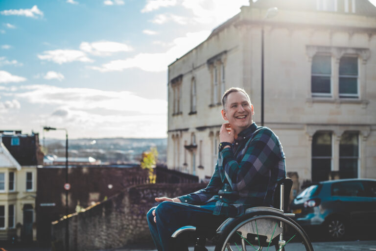 Stephen sits in his wheelchair in front of some buildings. He is wearing a blue checked shirt. He is smiling towards the middle distance